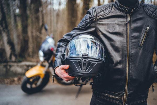 A motorcyclist holding a helmet