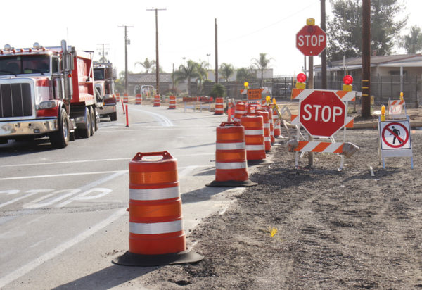Two large trucks drive through a work zone with cones and stop signs
