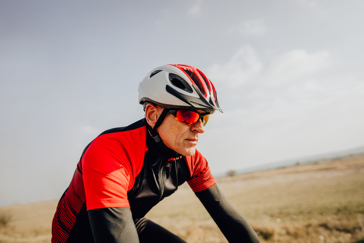 profile of cyclist with sunglasses and helmet riding up a hill