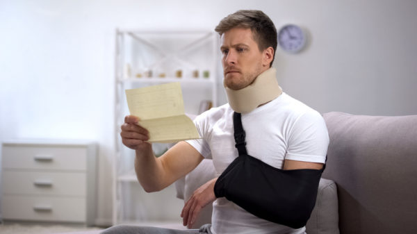 Man in foam neck brace and arm sling reading medical bill, shocking price
